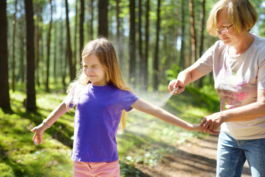 Middle age woman applying insect repellent to her granddaughter